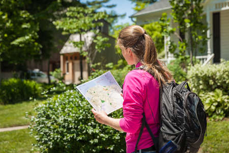the right path: Young beautiful woman with map in hand to find the right path in town Stock Photo