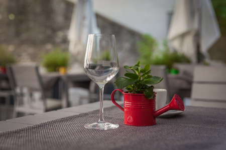 steel sheet: kettle of water as a decoration on a wooden table on the terrace restaurant