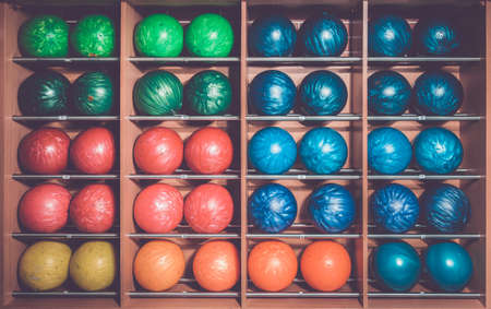 Bowling balls in the rack, sorted by size and color