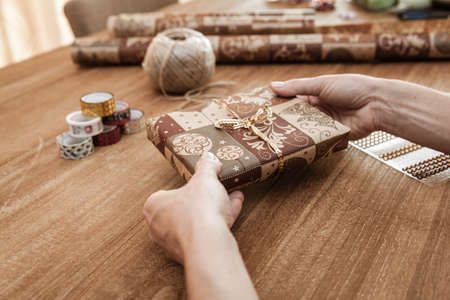 Time for gifts - gift box in hand girls on wood table Stock Photo - 115161547