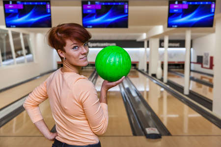 Beautiful young woman with bowling ball in a new bowling alley