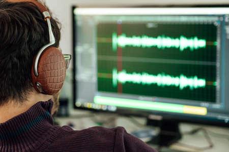 L'homme du studio photo enregistre et modifie le chant, la voix et la musique à des fins commerciales. Fonctionne dans un éditeur audio dans un ordinateur avec casque