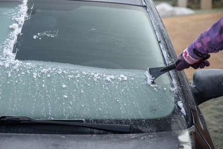 pulire il vetro ghiacciato in macchina con un raschietto nelle prime ore del mattino in inverno