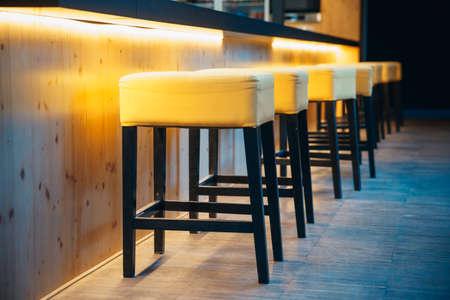 Taburetes en el mostrador de un bar nocturno para sentarse a los visitantes