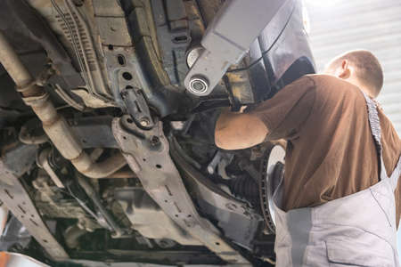 Repair and check car in repair shop. An experienced technician repairs the faulty part of the car. I change tires Banco de Imagens