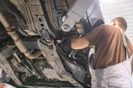 Repair and check car in repair shop. An experienced technician repairs the faulty part of the car. I change tires 版權商用圖片