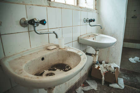 old dirty toilet in abandoned psychiatric hospital building. dirt and disorder on social facilities Banco de Imagens