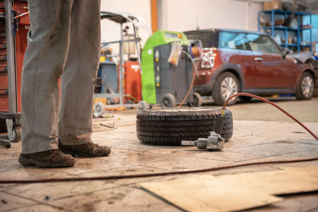Replacing winter tires on summer tires in a professional garage with the help of professional tools. Modern service. Banco de Imagens