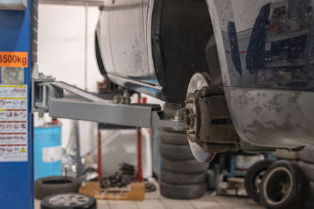 Repair and check car in repair shop. An experienced technician repairs the faulty part of the car. I change tires Imagens