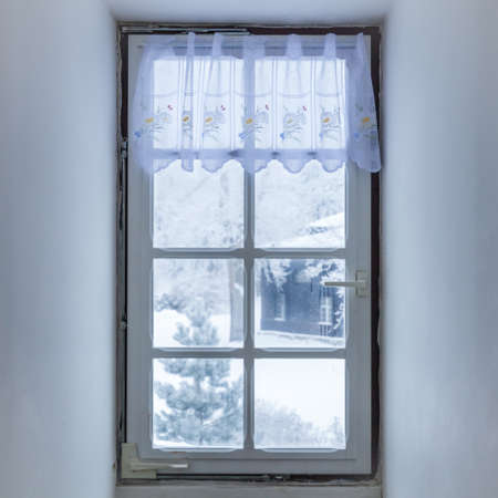 Fenster im Zimmer im Winter mit frostigem Mosaik bedeckt. Frostmuster auf Glas. Handabdrücke Standard-Bild