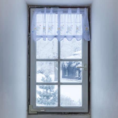 Finestra nella stanza ricoperta di mosaico gelido in inverno. Motivi di brina su vetro. Impronte di mani Archivio Fotografico