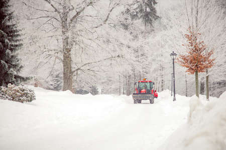 big tractor cleans road from snow in the winter. seasonal work Imagens