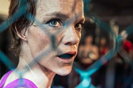 Wunderschöne Frau, mma-Kämpferin im Fitnessstudio während des Trainings. Vorbereitung auf einen harten Käfigkampf. Sexy Kämpfermädchen, das aktiv stanzt. Aggressiv und kampfbereit. Standard-Bild