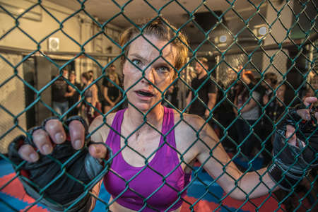 Gorgeous woman, mma fighter in gym during training. Preparing for a hard caged match. Sexy fighter girl punching actively. Aggressive and ready to fight.