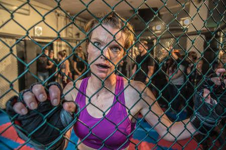 Wunderschöne Frau, mma-Kämpferin im Fitnessstudio während des Trainings. Vorbereitung auf einen harten Käfigkampf. Sexy Kämpfermädchen, das aktiv stanzt. Aggressiv und kampfbereit.