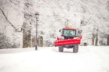 duży traktor czyści drogę ze śniegu w zimie. Praca sezonowa