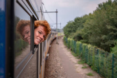 A young woman travels on a train to discover new places of interest in the world