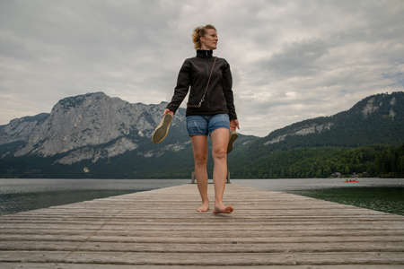 young woman with her dog enjoying the atmosphere of a mountain lake on the pier Banco de Imagens