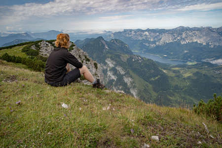 A young woman relaxes with a view of a mountain lake after a busy hike 写真素材 - 132915750