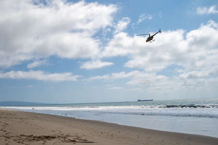 Helicopter patrols over the ocean beach