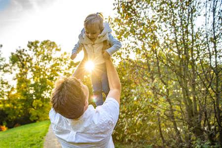 Szczęśliwy tata z córką cieszą się jesienią w parku przy pięknej pogodzie