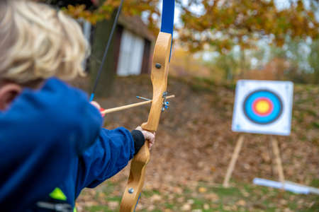 Children shot on target during a competition in archery in the forest in fall
