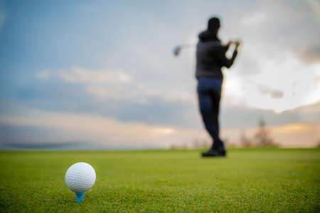 golfer on a green pitch batting golf ball.