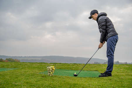 golfer on a green pitch batting golf ball