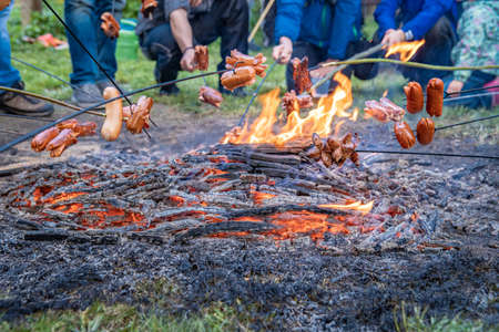 grilling sausages on an open fire with large family gatherings Reklamní fotografie