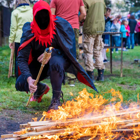 executioner lights a torch by the fire for burning the witch. Stock Photo