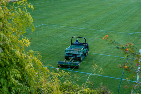 cutting the grass before the game on the football field with a tractor