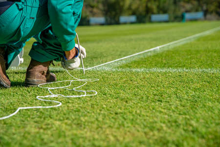 Stretching a rope for lining a football field using white paint on the grass.