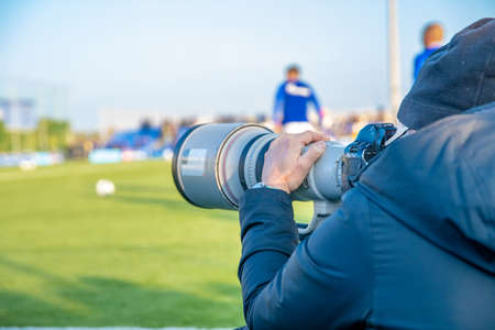 photoreporter with telephoto lens on a football match Foto de archivo