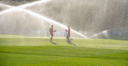 Football players collect balls after football training. watering the football field.