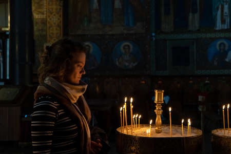 woman in the church prays before candles, worship