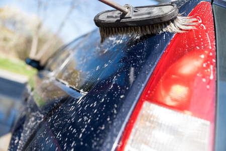 Hand wash the car using a brush with foam