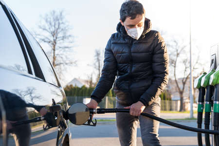 fueling the car at the time of the epidemic coronavirus with a respirator over his mouth and nose