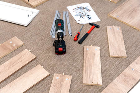 Assembling furniture at home after shopping in the store using a screwdriver and hammer.