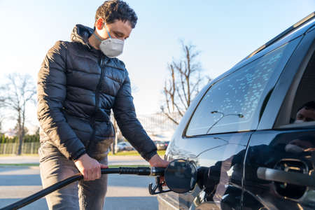 fueling the car at the time of the epidemic coronavirus with a respirator over his mouth and nose Reklamní fotografie
