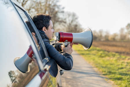 a young man brought into megaphone important news through a car window.