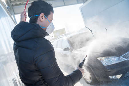 washing car by water pressure at self-service station. A man with a respirator on the face protects against a coronavirus epidemic