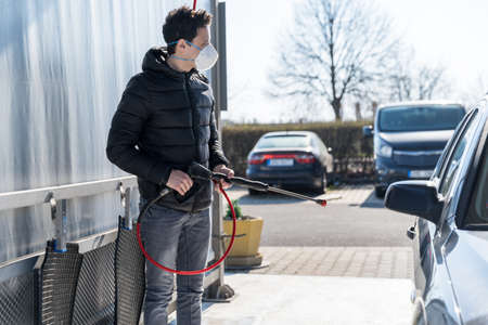 washing car by water pressure at self-service station. A man with a respirator on his face protects himself from a viral epidemic.