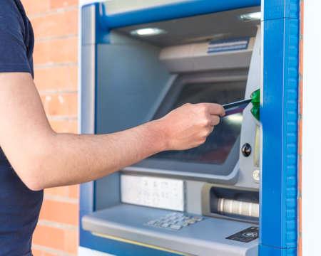 Retirer de l'argent à un guichet automatique en utilisant une carte de crédit. Banque d'images