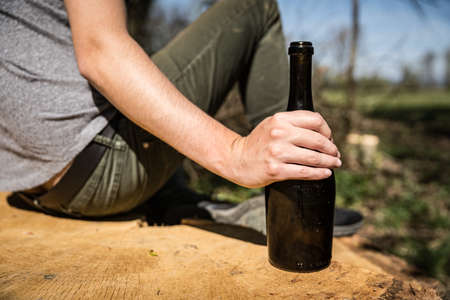 a bottle of wine in a mans hand, drinking alcohol in nature