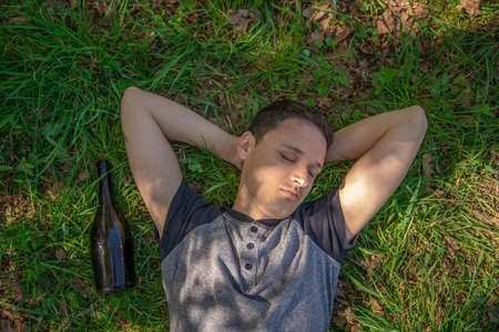 drunk man sleeping on a green field after using alcohol, a bottle lying next to a man 스톡 콘텐츠