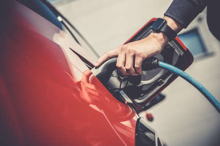 The man charges the electric car at the charging station. Stockfoto