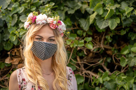 wedding portrait of a woman in a dress with a floral wreath on her head and a mask on her mouth. measures at the time of the coronavirus epidemic
