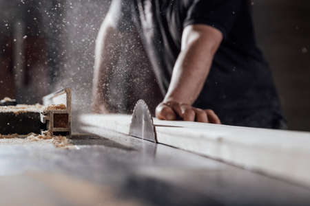 A man cuts wood on a circular saw in a joinery