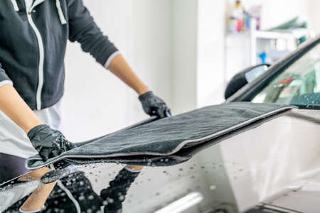 wiping water from the car hood with a microfiber cloth