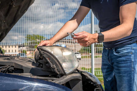 The man changes the bulb in the headlight of a car